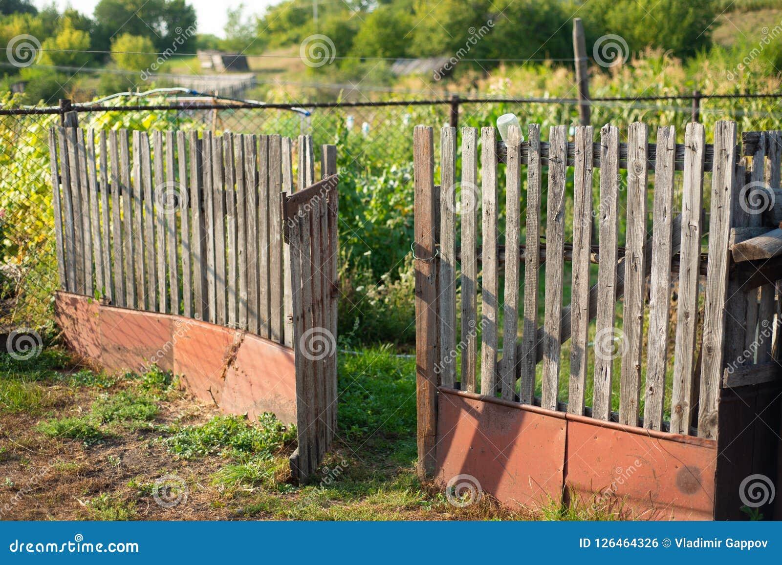 在一个农场的老篱芭在村庄 开放的门
