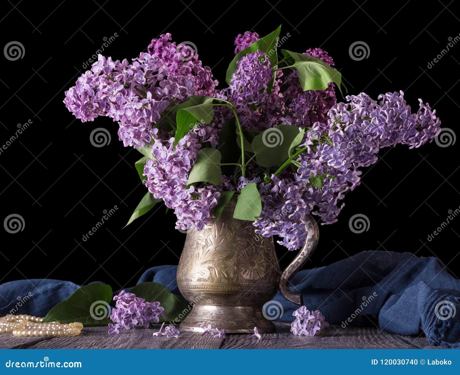 在一个古老花瓶的丁香,在蓝色织品和小珠旁边,在黑色