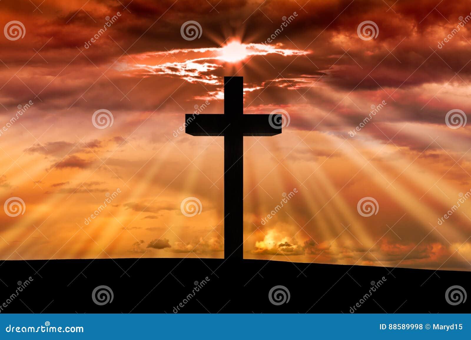 在一个场面的耶稣基督木十字架与深红橙色日落,