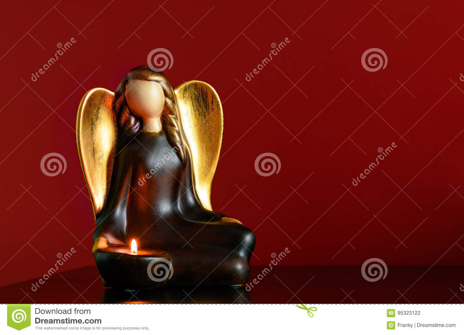 在一个床头柜的天使形象烛台与一灼烧的candl