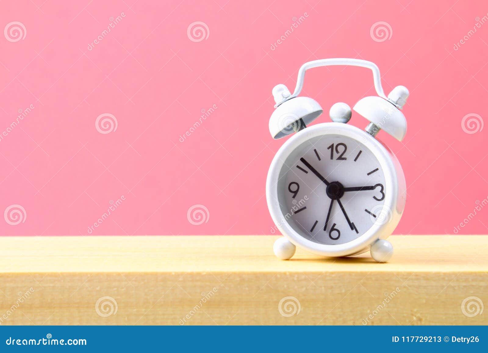 在一个木架子的白色小闹钟在桃红色淡色背景 简单派