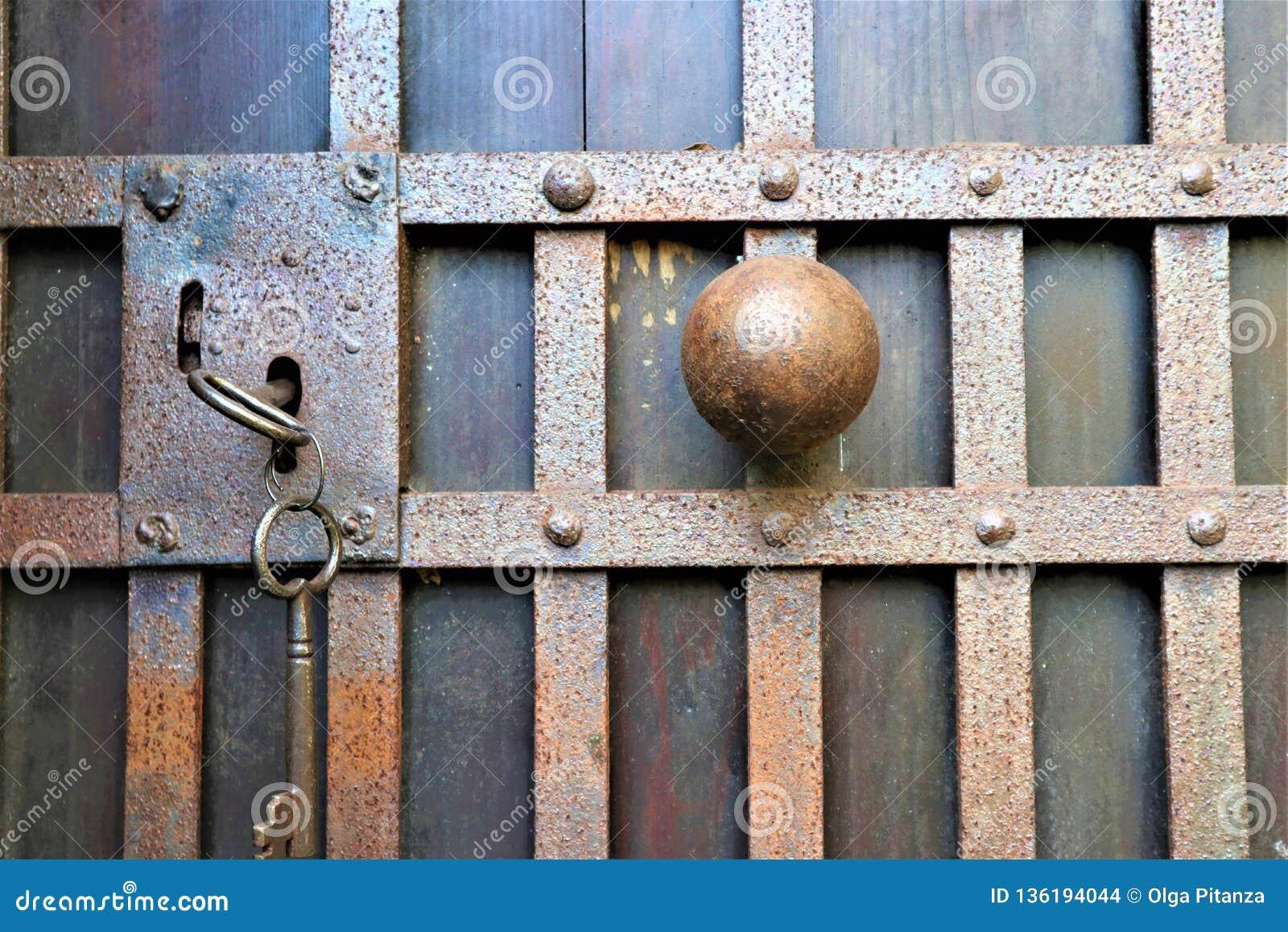 在一个木门的闭合的老生锈的挂锁