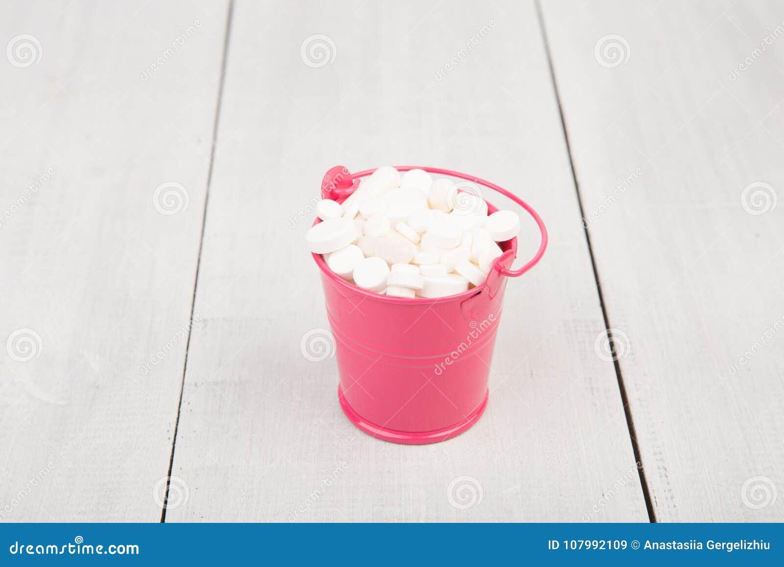 在一个桃红色桶的许多不同的白色药片在木书桌上