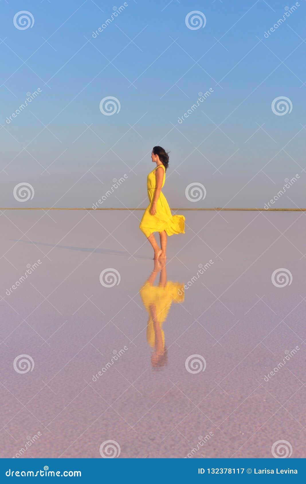 在一个桃红色盐湖中间的一年轻女人在一件明亮的黄色礼服站立并且遇见日落