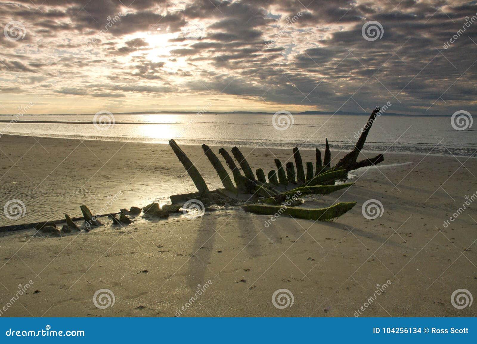 在一个海滩的海难在日落