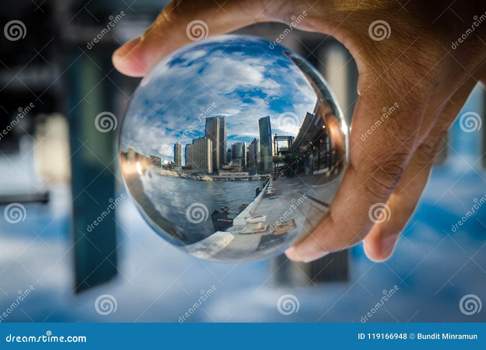 在一个清楚的玻璃水晶球的都市风景摄影与剧烈的云彩天空