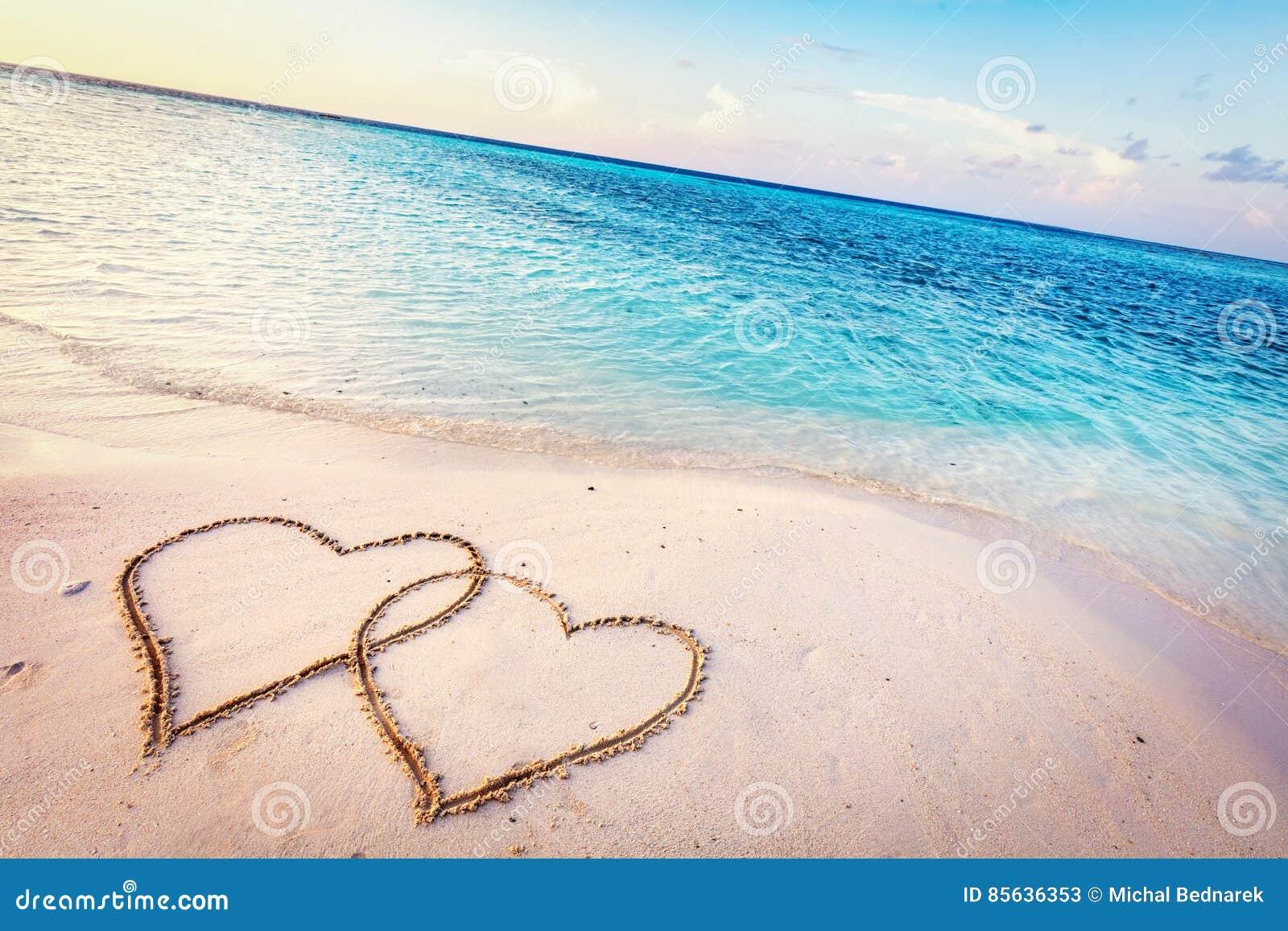 在一个热带海滩的沙子画的两心脏在日落