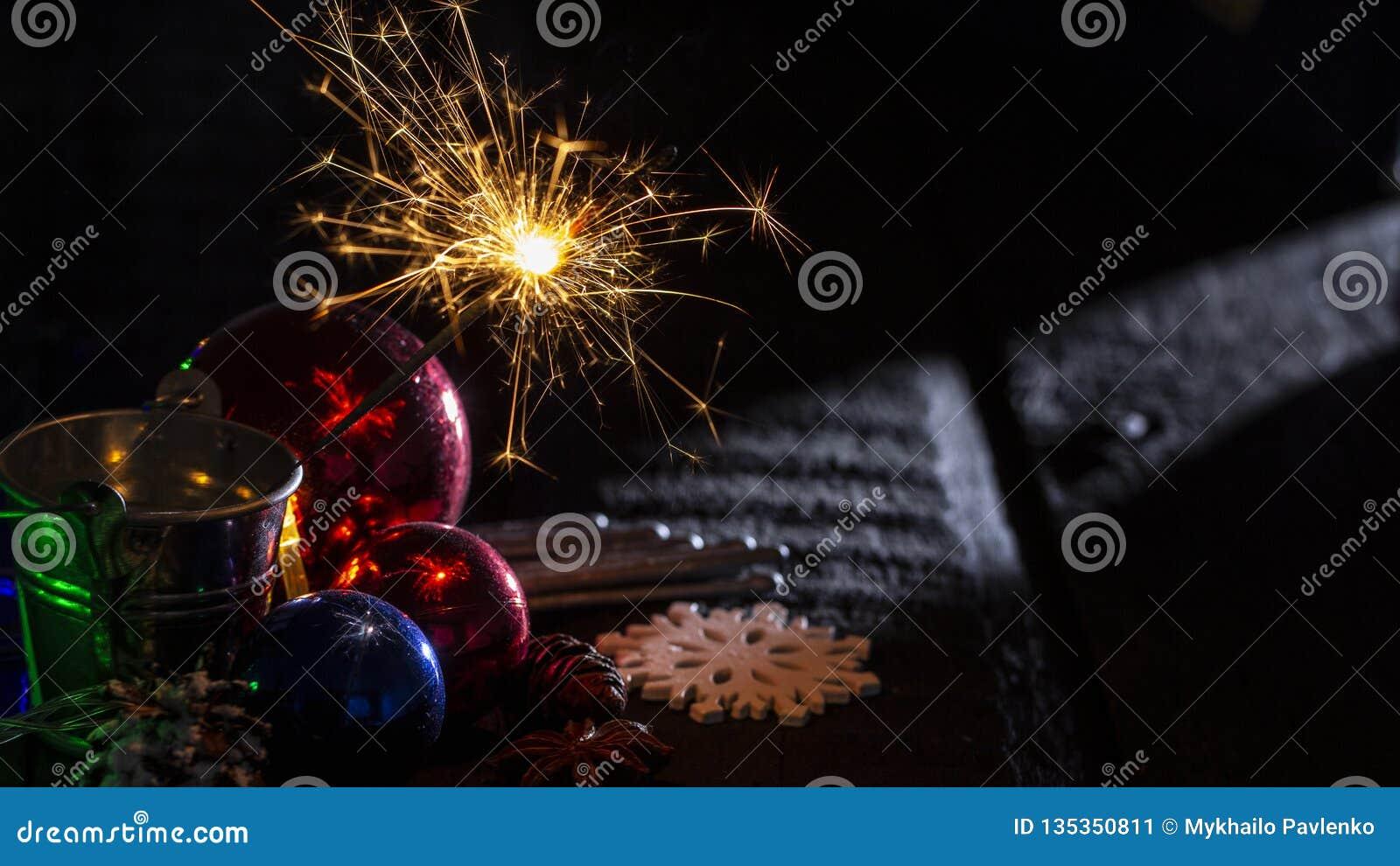 在一个玻璃球后的燃烧的闪烁发光物在黑木背景