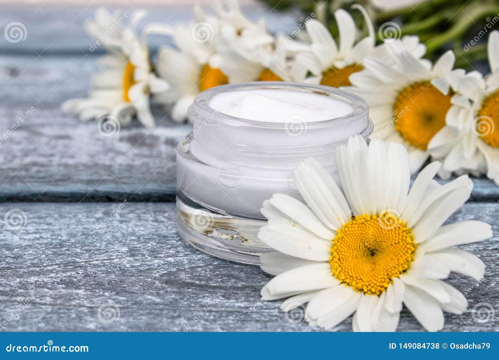 在一个玻璃瓶子的化妆奶油在雏菊附近站立