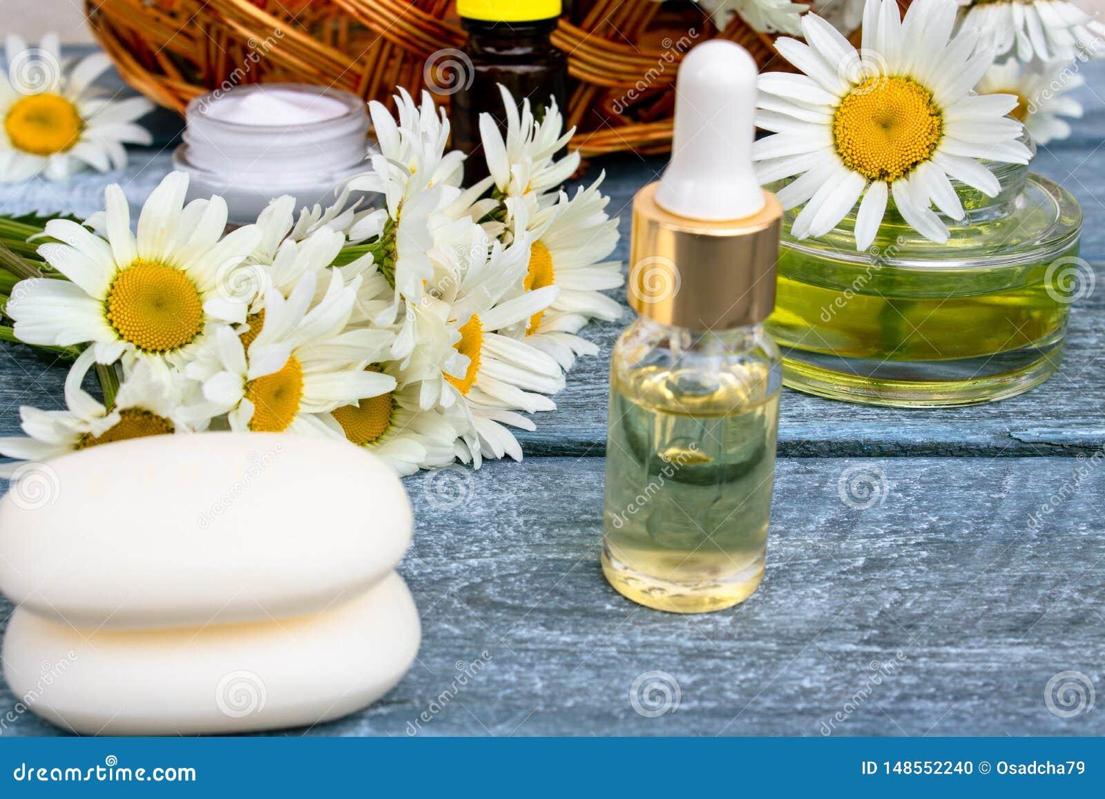 在一个玻璃瓶子的春黄菊精油在春黄菊和化妆肥皂旁边