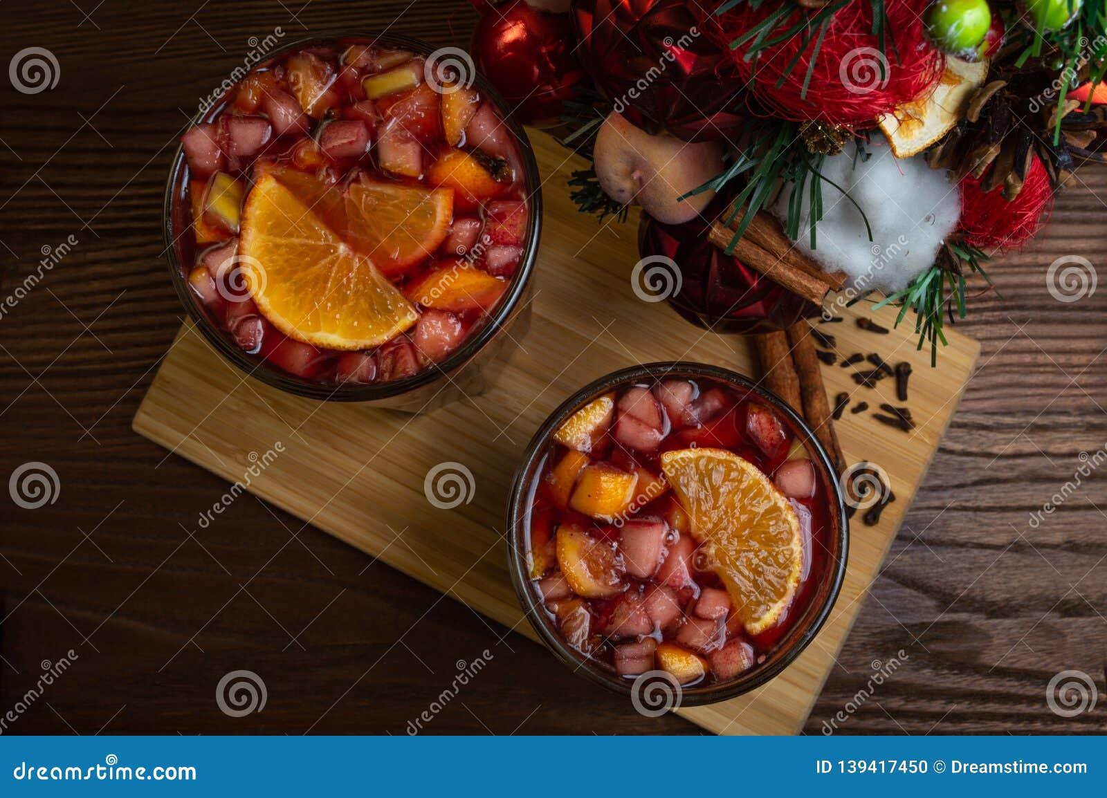 在一个玻璃觚,加香料的热葡萄酒的芬芳辣传统饮料,与圣诞树、香料和新鲜水果