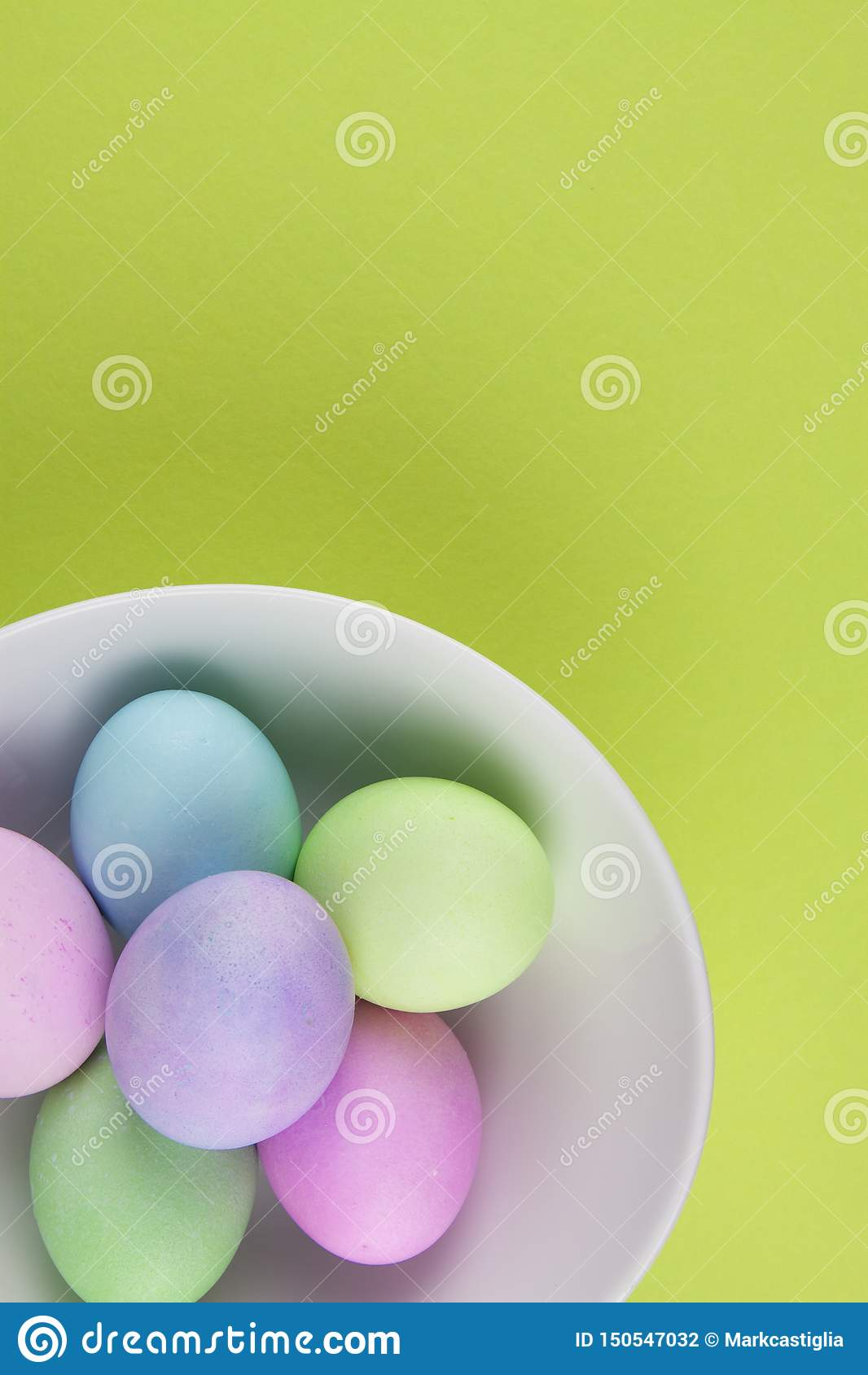 在一个白色碗的明亮地被绘的复活节彩蛋顶上的看法在绿色背景