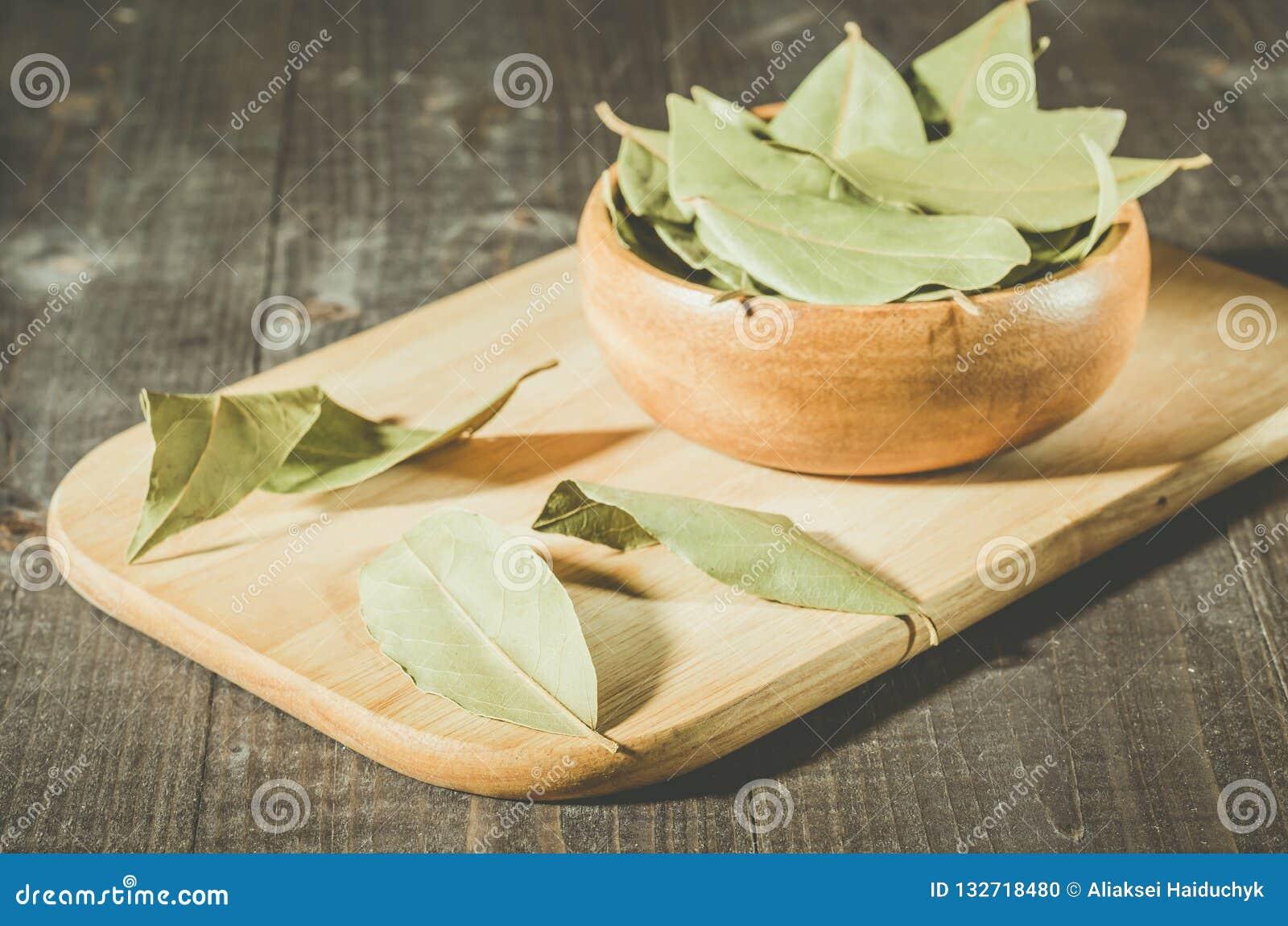 在一个盘子的月桂叶在一片木碗/月桂叶在一块木板材o