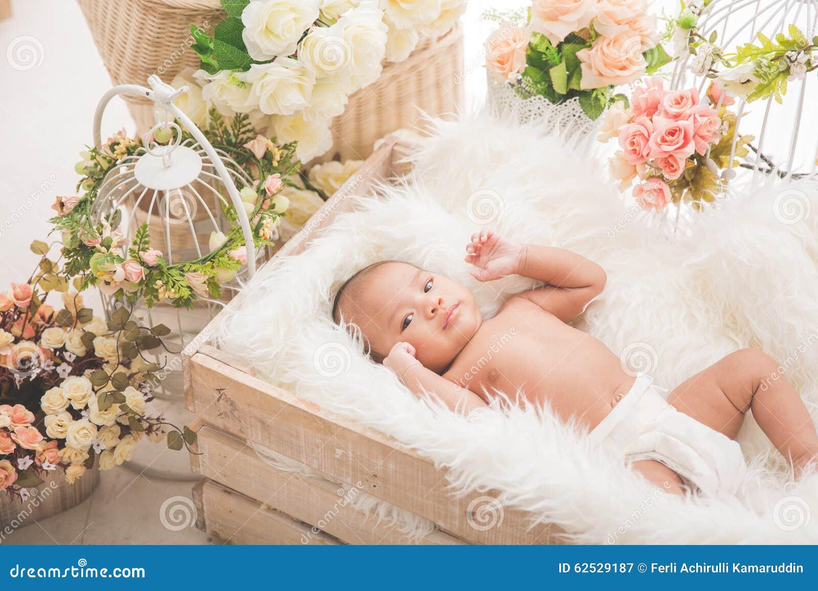 在一个箱子里面的亚裔女婴有白色毯子的,花aroud
