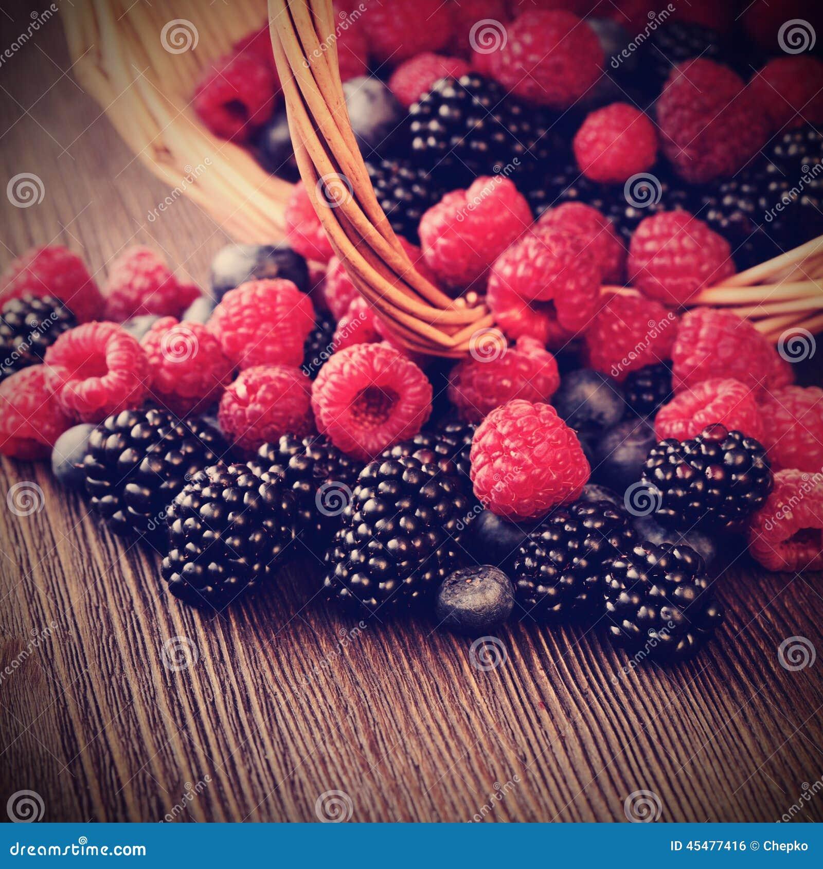 在一个篮子的不同的莓果在一张木桌上