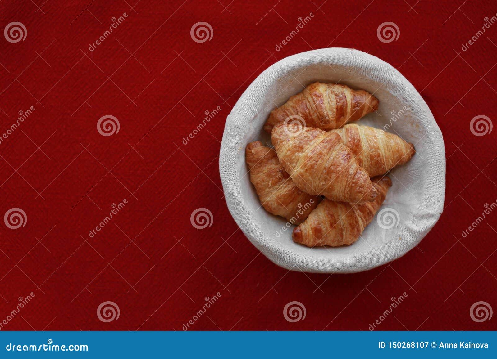 在一个篮子的新近地被烘烤的新月形面包在红色
