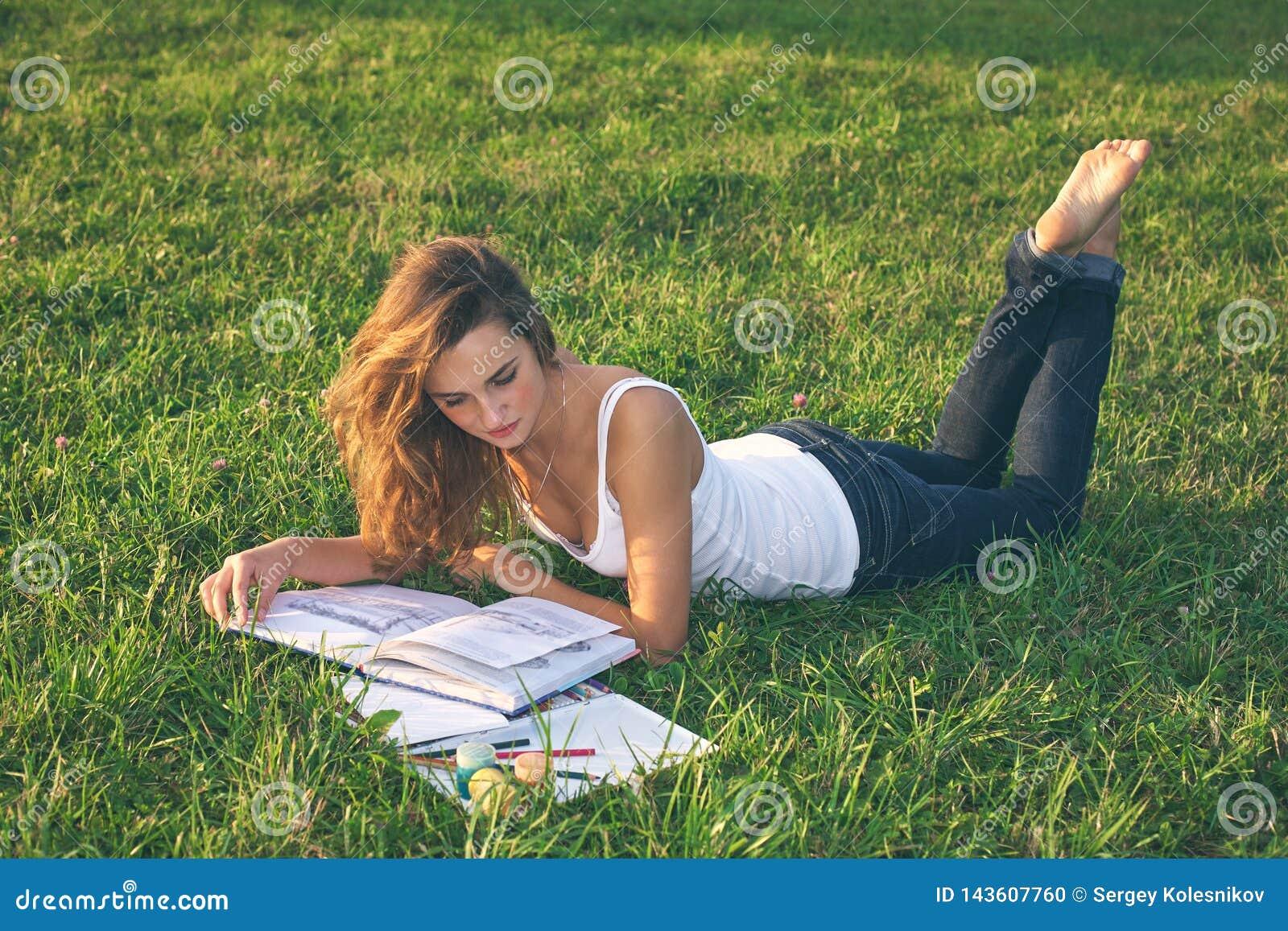 在一个绿色草甸的美好的年轻女人读书