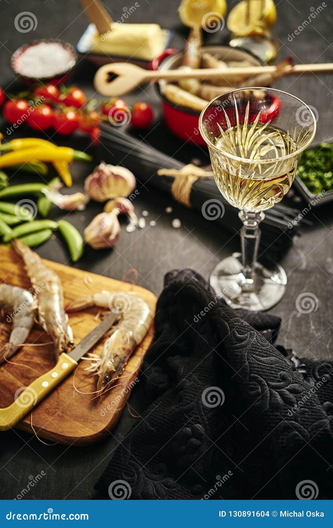 在一个罐的新鲜的可口未加工的老虎大虾用荷兰芹、柠檬、黄油、蕃茄和辣椒和酒