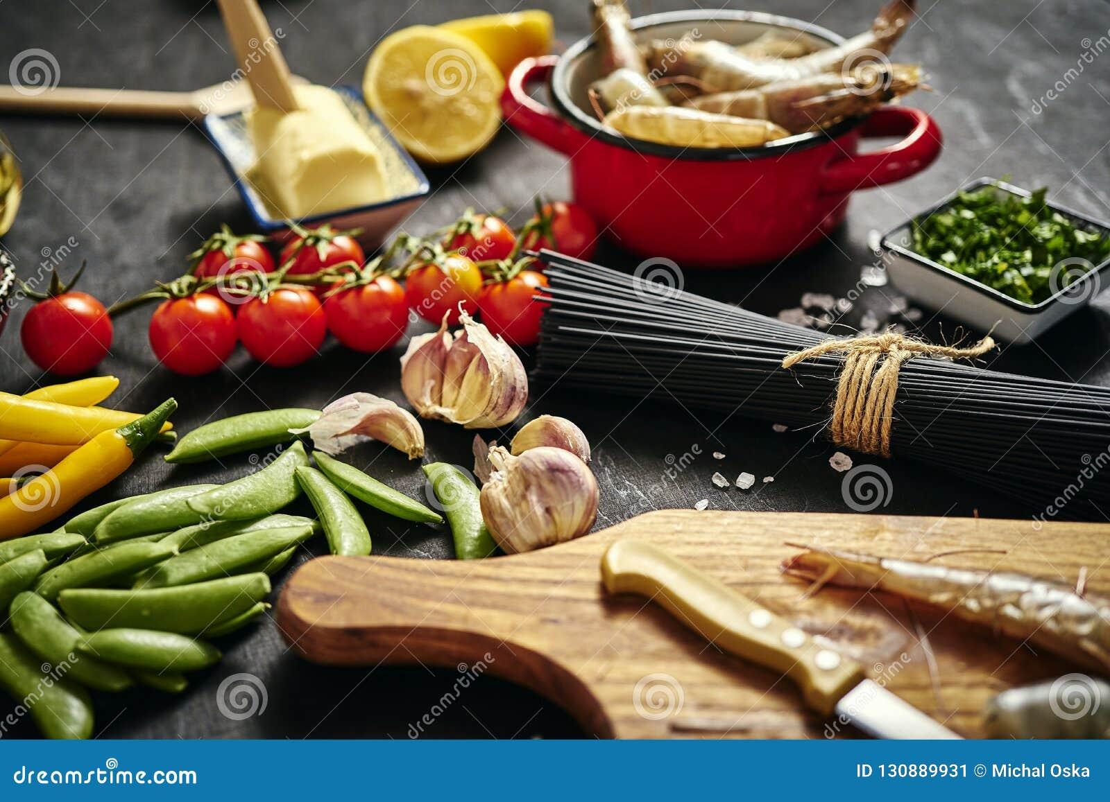 在一个罐的新鲜的可口未加工的老虎大虾用荷兰芹、柠檬、黄油、蕃茄和辣椒