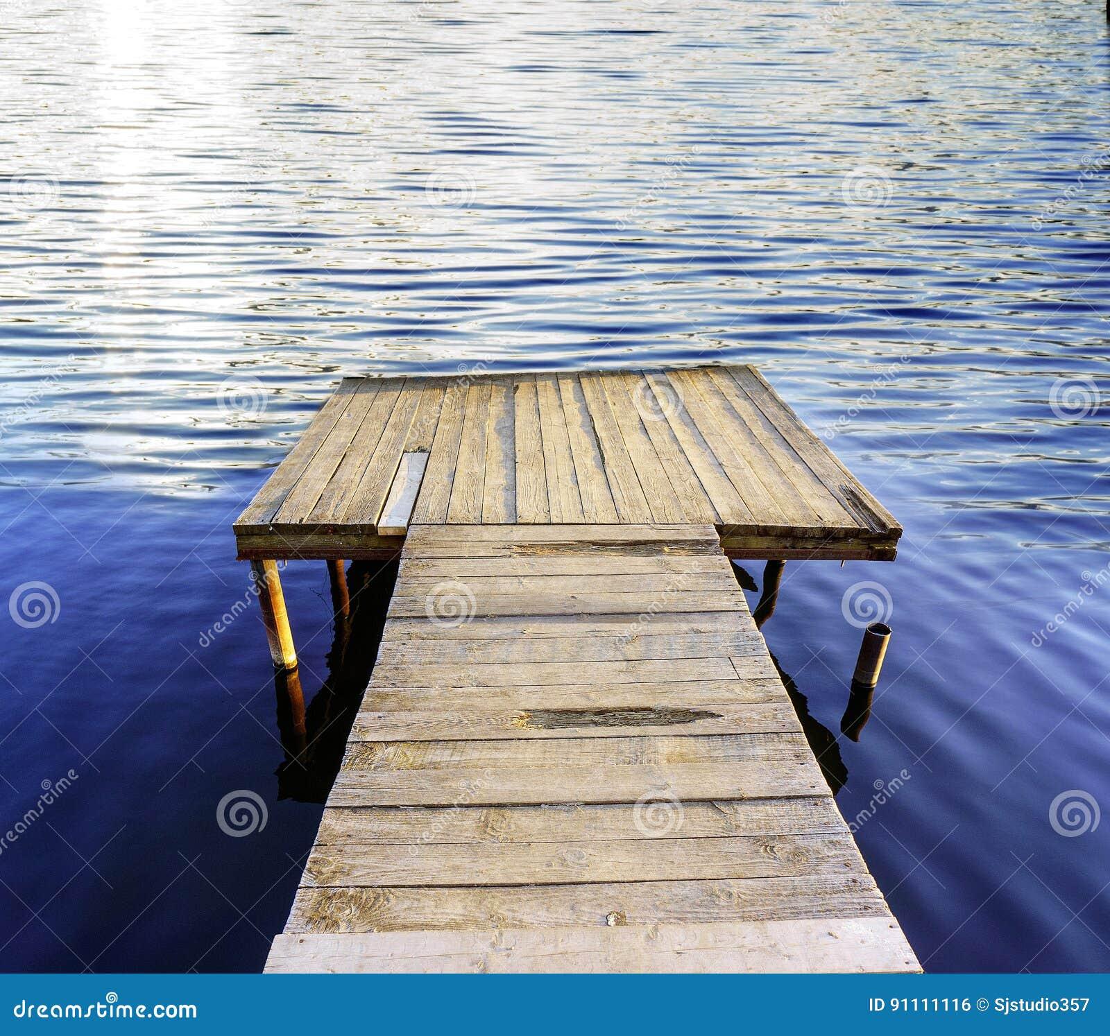 在一个蓝色镇静湖的码头,背景