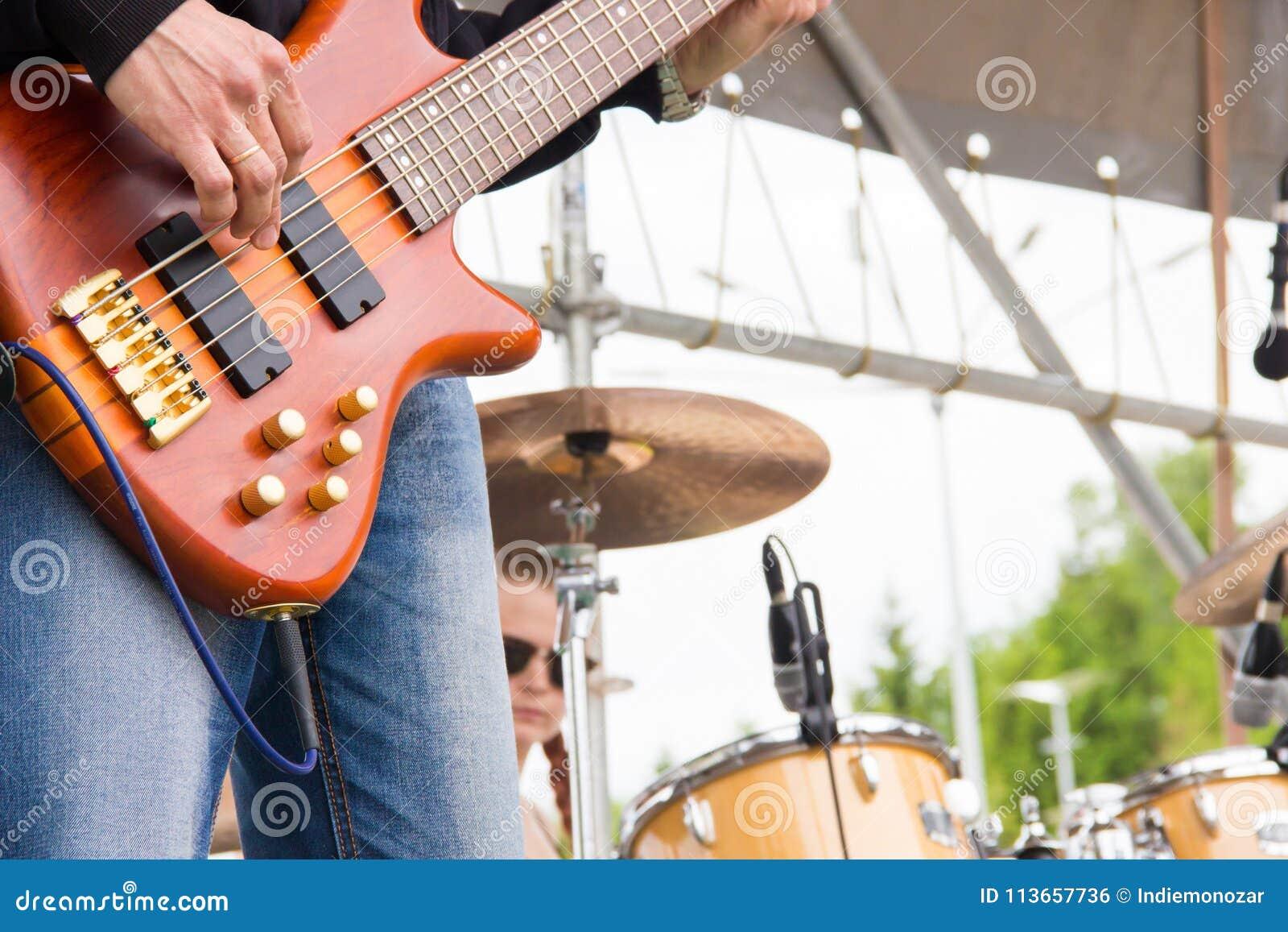 在一个露天节日的音乐带perfom 使用低音吉他弹奏者的人紧密,模糊的鼓