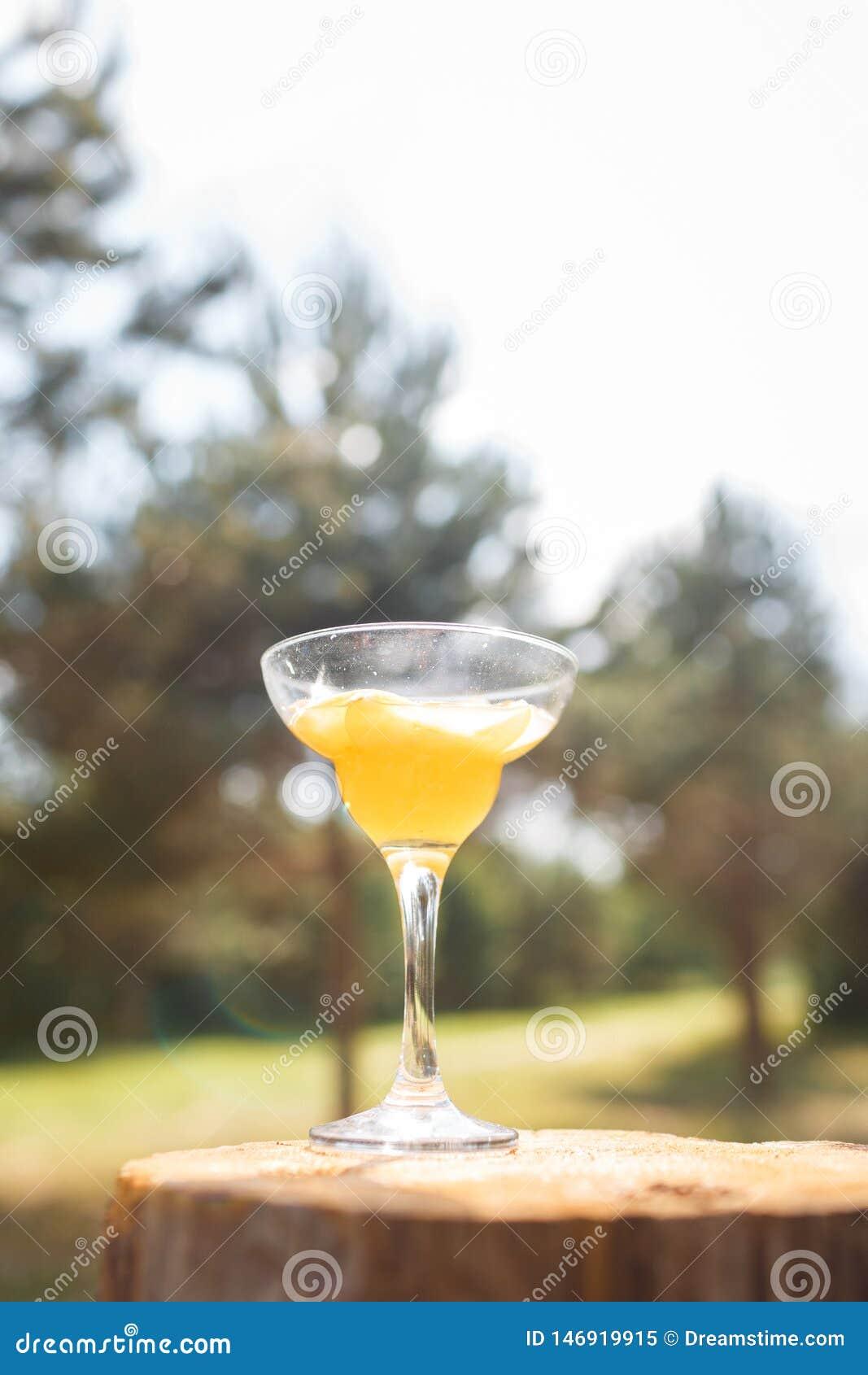 在一个高词根的一块玻璃与一份黄色饮料