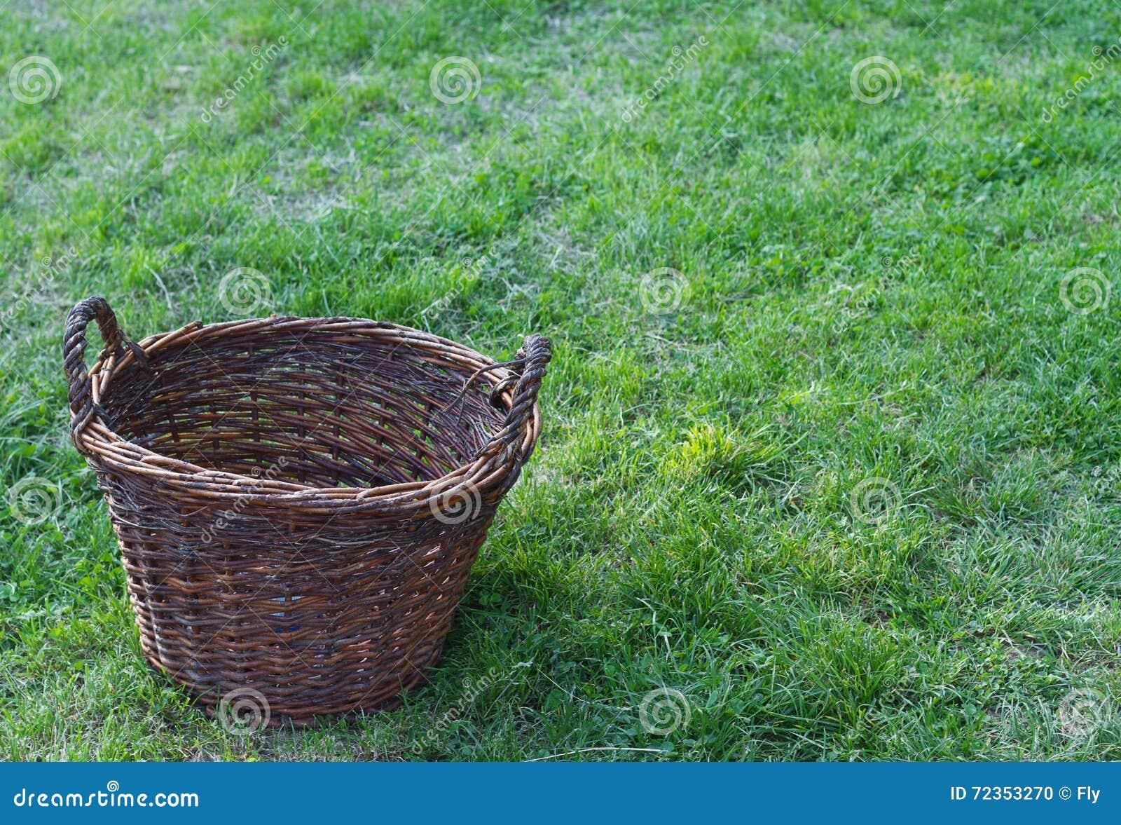 在一个绿色领域的一个木空的土气篮子