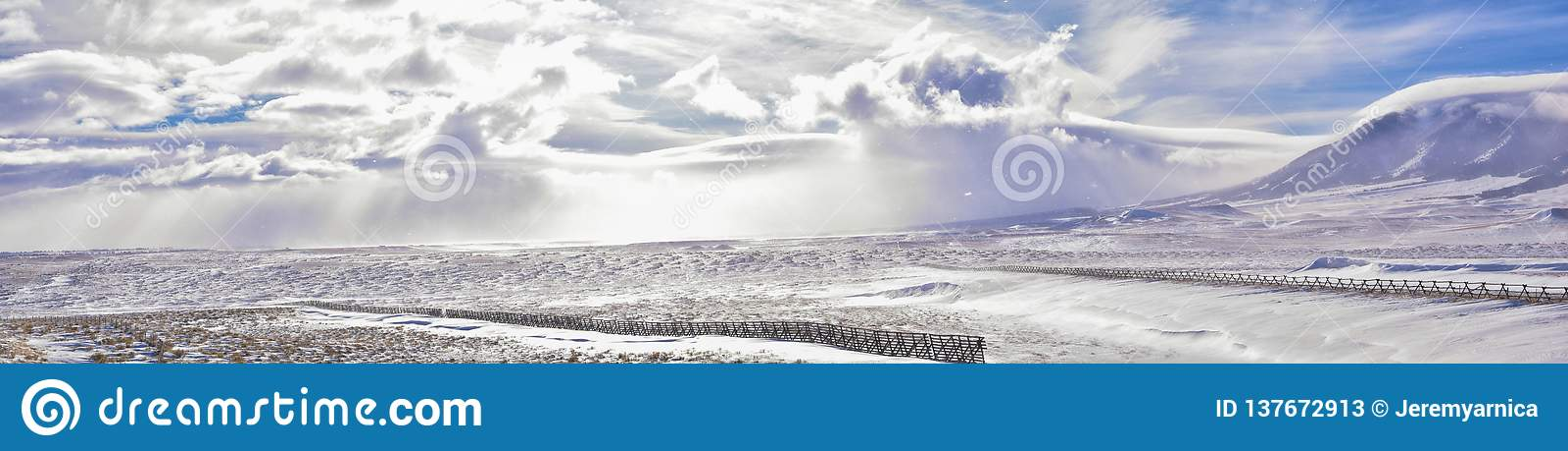 在一场飞雪期间的怀俄明乡下全景与与积雪的山与阴云密布灰色多云天空