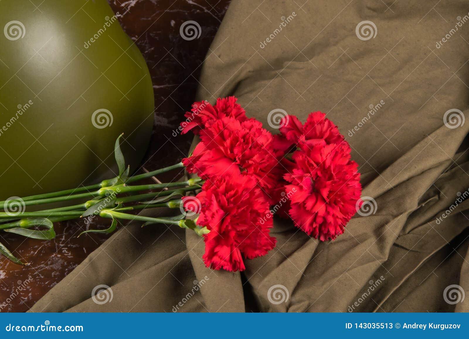 在一块大理石平板、红色康乃馨花束,一件军事盔甲和斗篷帐篷上