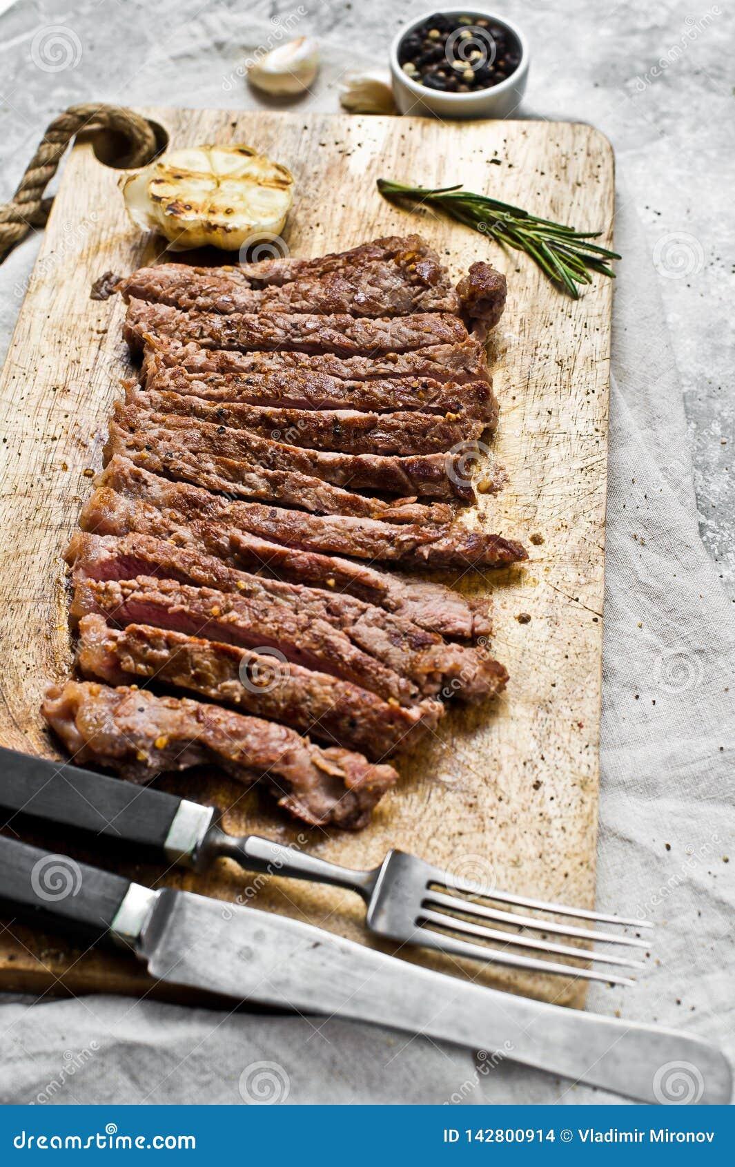 在一块木砧板的牛后腹肉排 灰色背景,顶视图,文本的空间