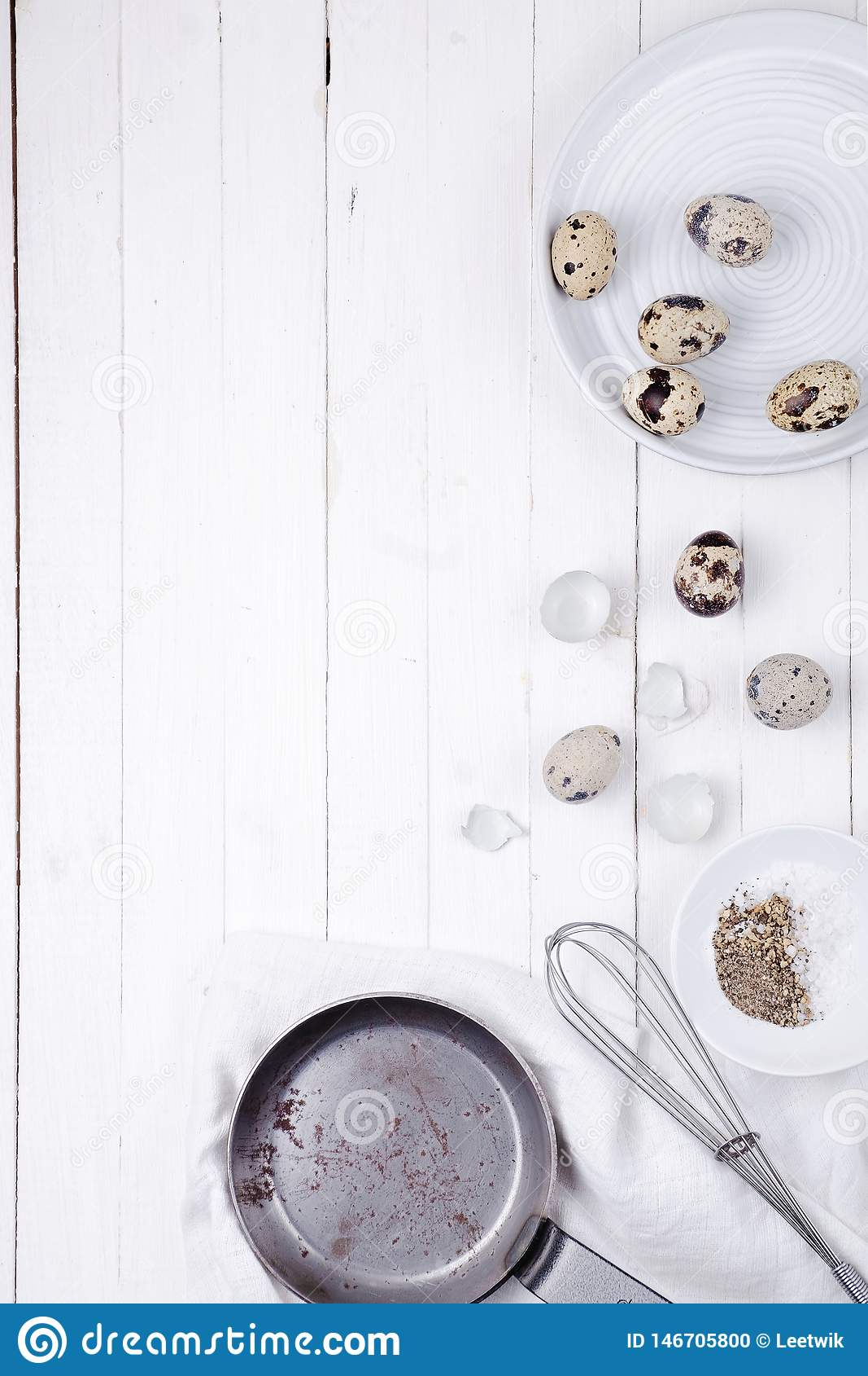在一块板材、壳、一飞奔打的和一个煎锅的鹌鹑蛋在白色木背景 o