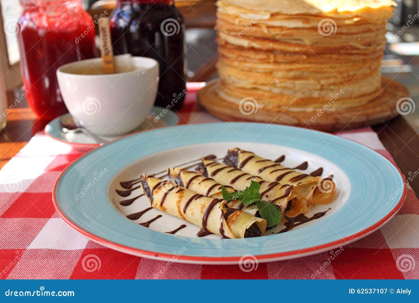 在一块板材的滚动的薄煎饼用蜂蜜