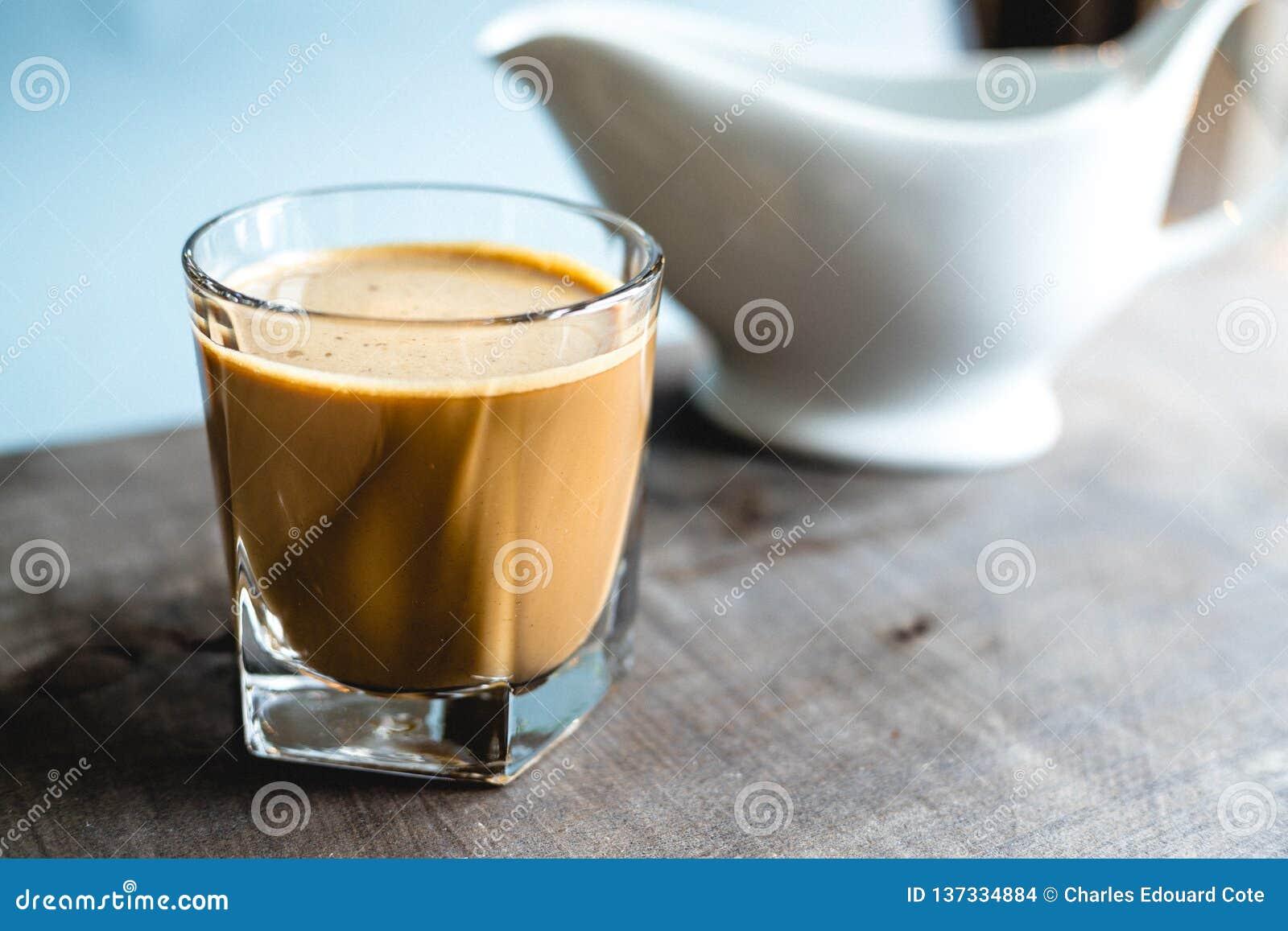 在一块玻璃的咖啡在一张木桌上