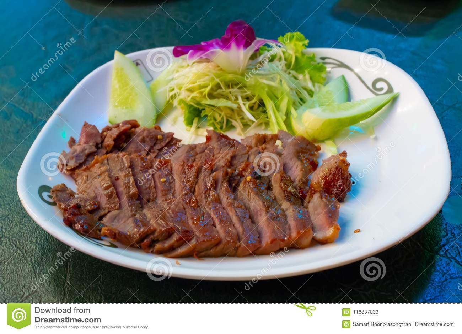 在一块白色板材的烤牛肉用调味汁和菜