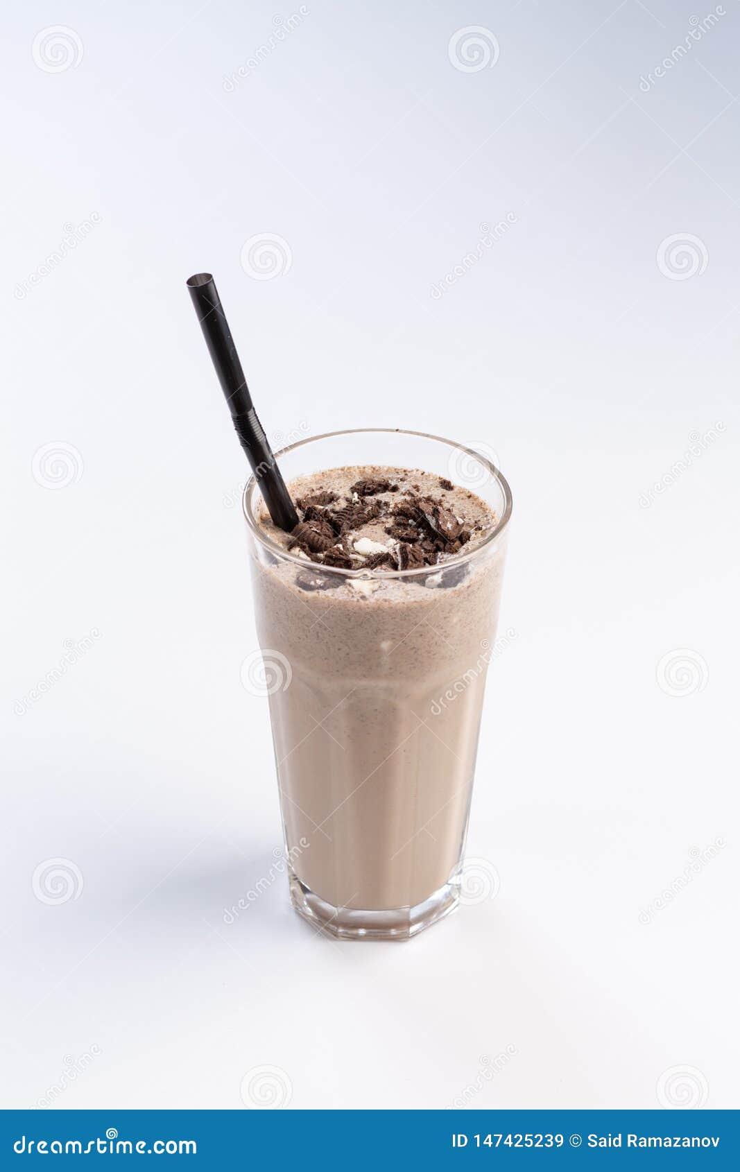 在一块高玻璃的牛奶巧克力鸡尾酒与在白色背景的秸杆