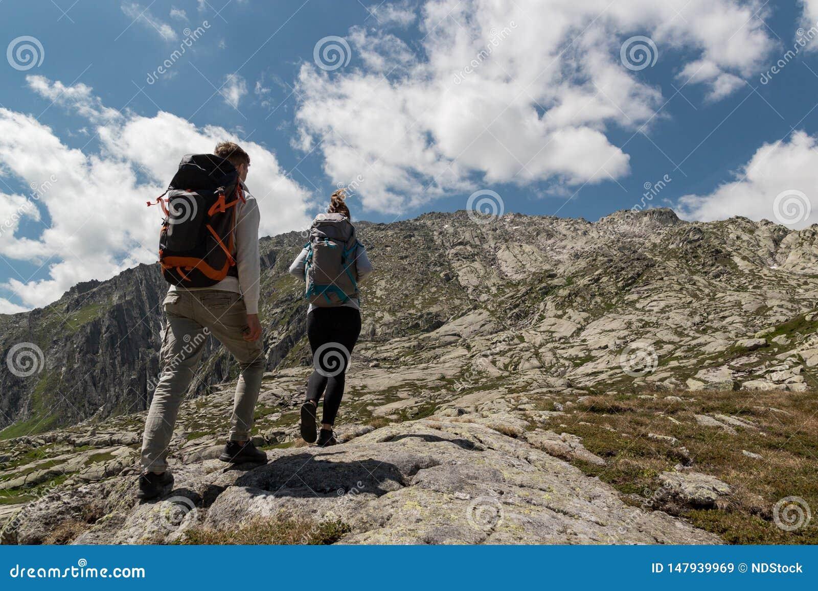 在一好日子期间,年轻加上走大的背包到达山的上面