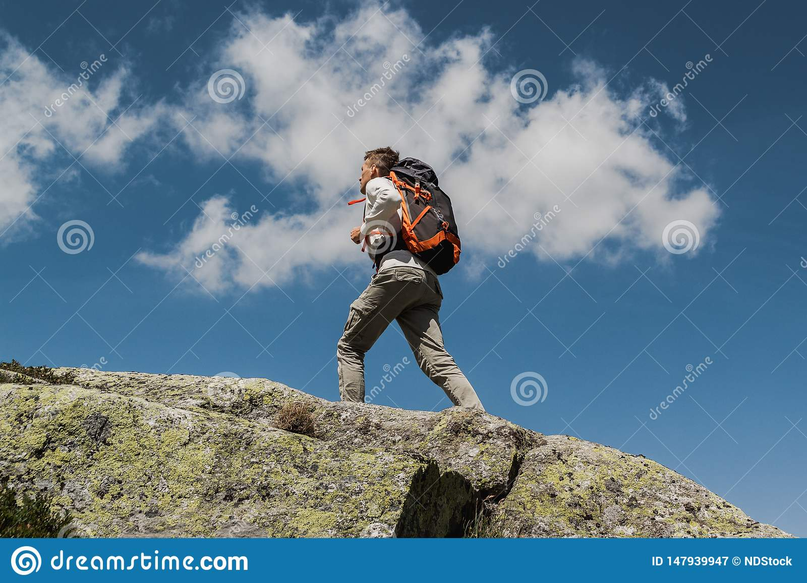在一好日子期间,有大背包的走的年轻人到达山的上面