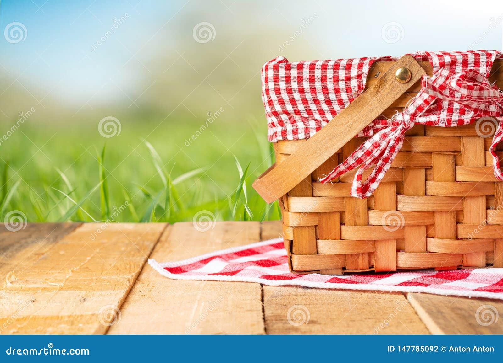 在一张木桌上的野餐篮子与桌布 放松在野餐,和令人愉快本质上,与空间