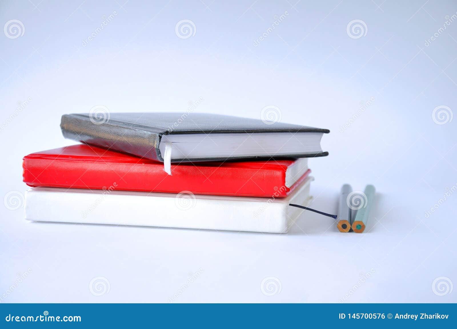在一张桌上的几个笔记本与在白色背景的一支铅笔