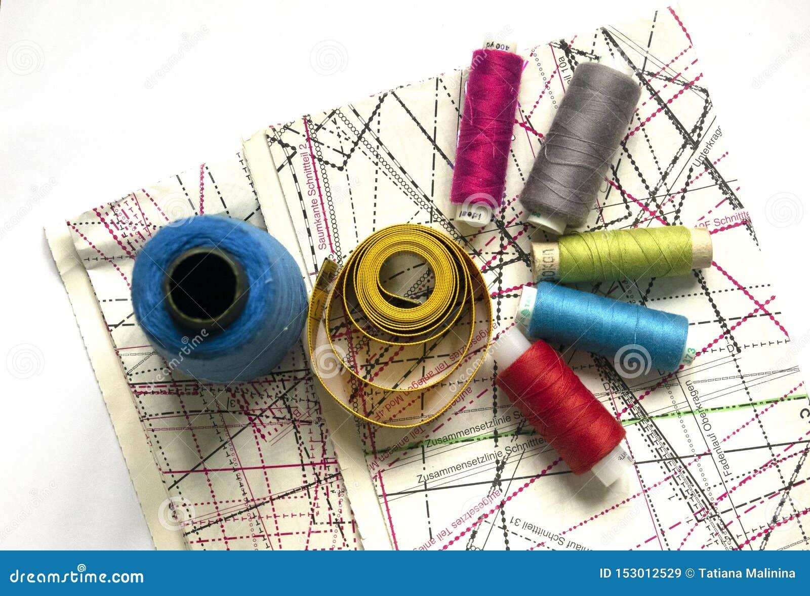 在一张白色木桌上的缝合的供应:缝合针线,剪刀,螺纹,布,针,厘米一个大短管轴