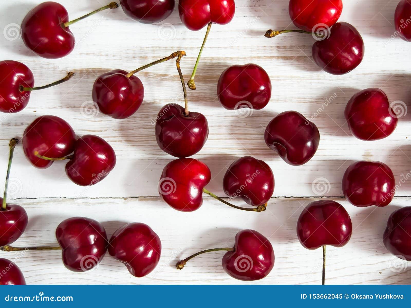 在一张白色木桌上驱散的红色樱桃莓果