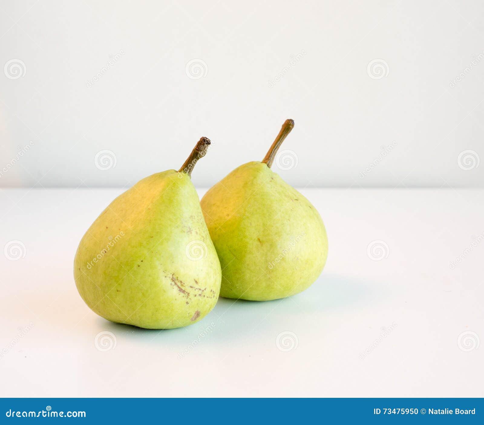 在一张白色桌上的两个绿色梨