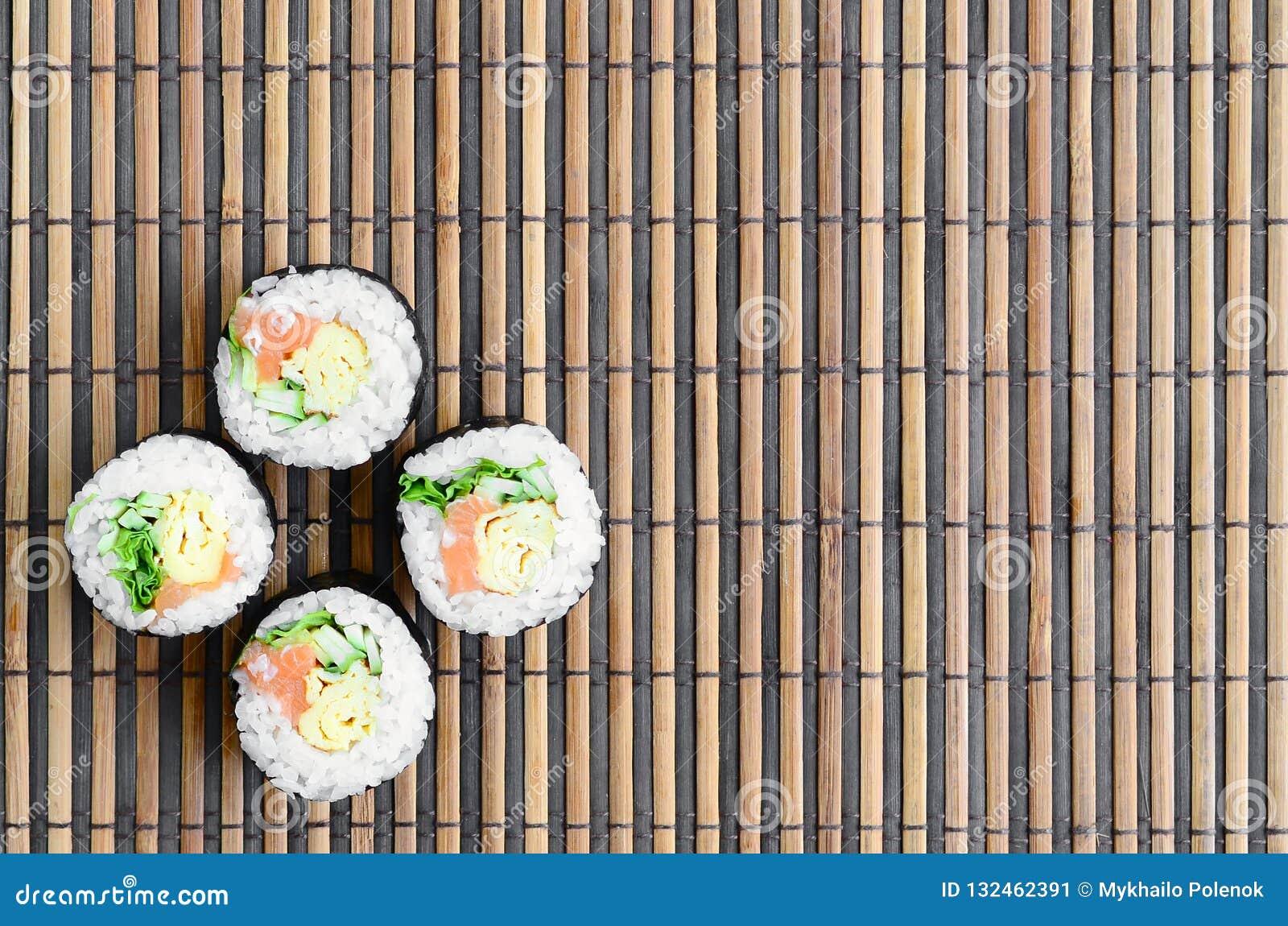 在一张竹秸杆serwing的席子寿司卷谎言 亚洲食物炒饭传统蔬菜 顶视图 与拷贝空间的平的被放置的简单派射击