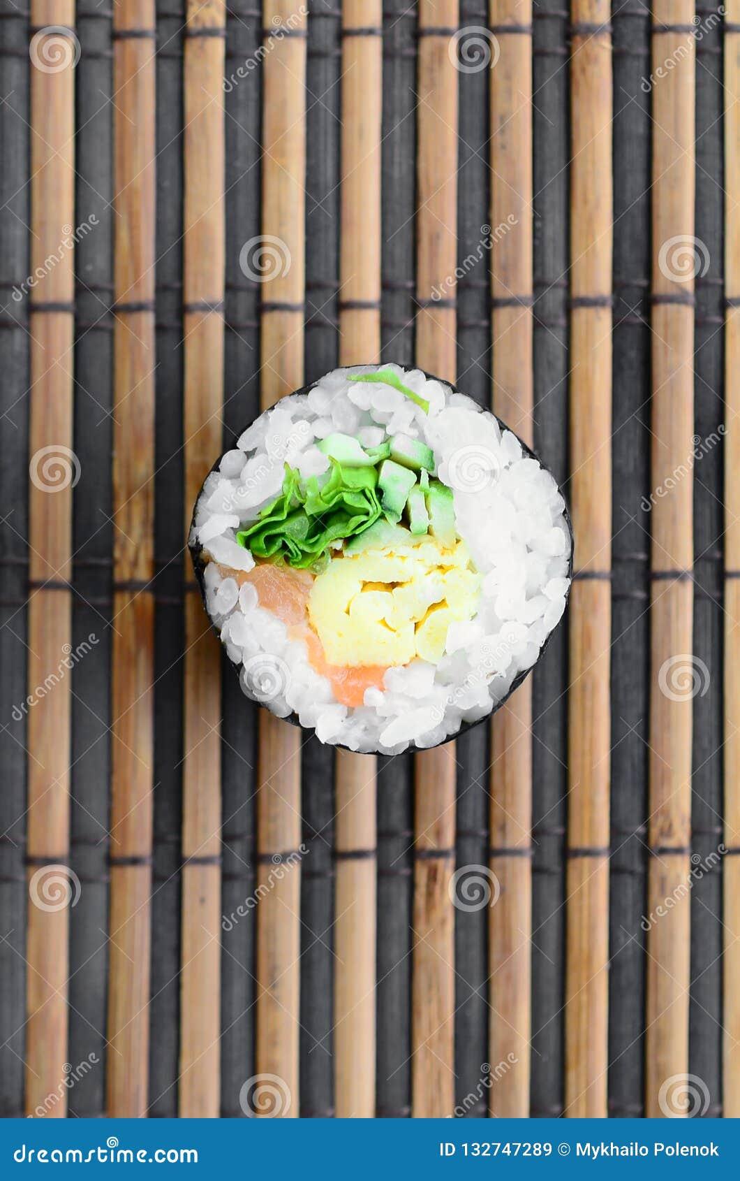 在一张竹秸杆serwing的席子的寿司卷谎言 亚洲食物炒饭传统蔬菜 顶视图 与拷贝空间的平的被放置的简单派射击