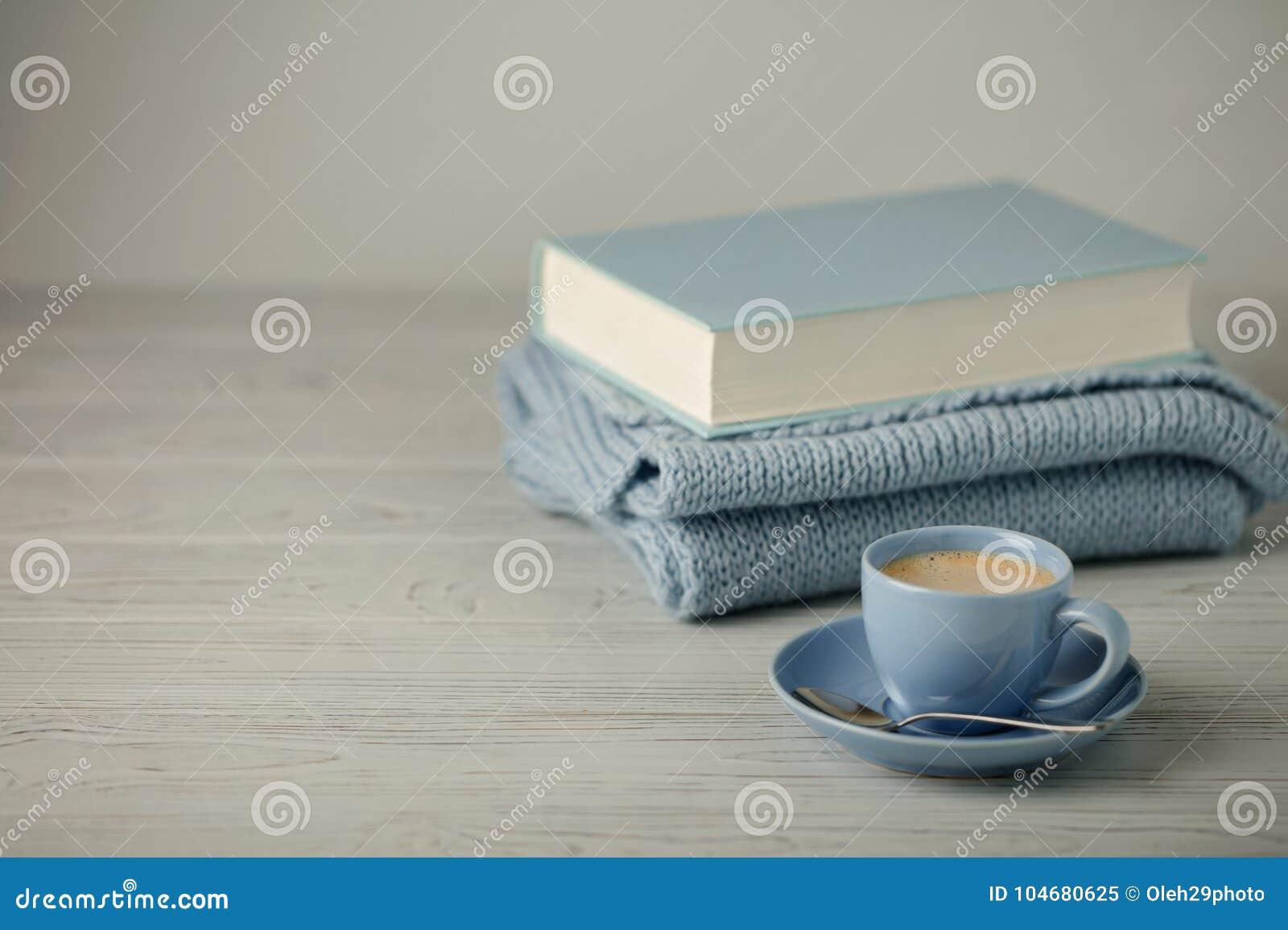 在一本浅兰的杯子和书的咖啡在与knitt的蓝色捆绑