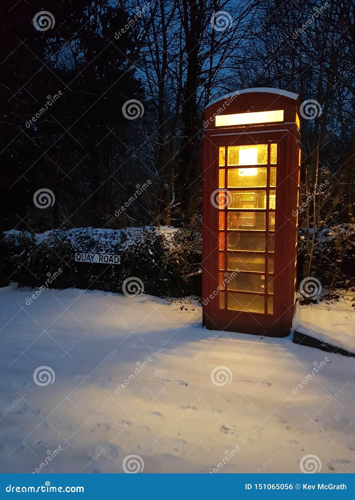 在一条积雪的村庄街道上的电话亭