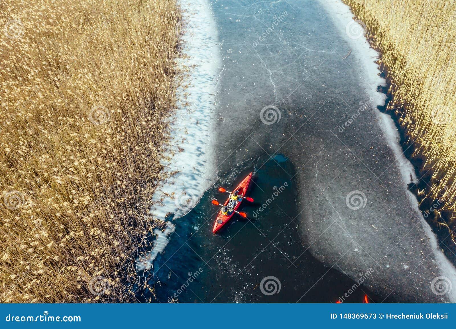 在一条红色小船的两个运动人浮游物在河
