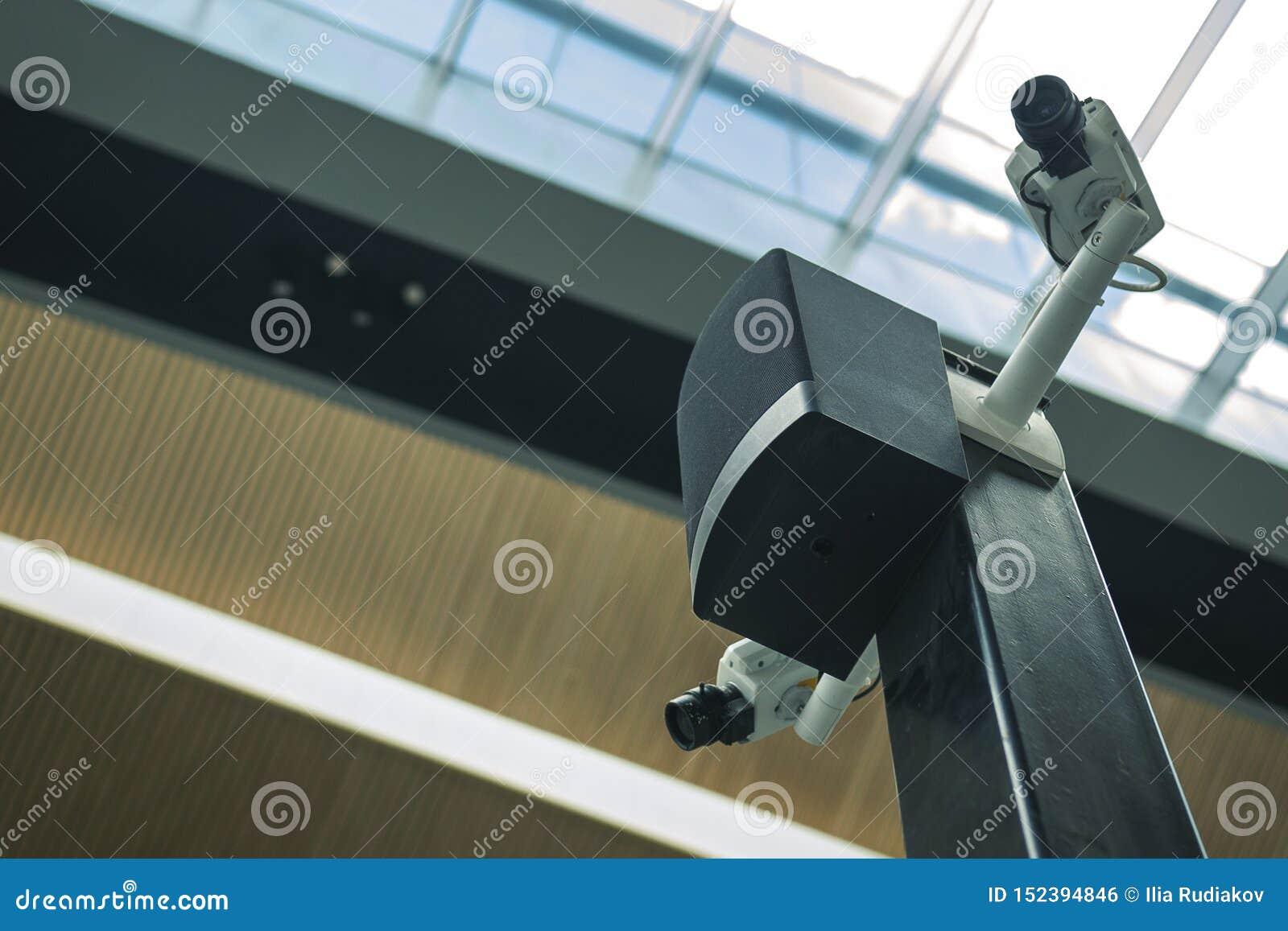 在一根黑柱子的两部白色安全监控相机在机场前提