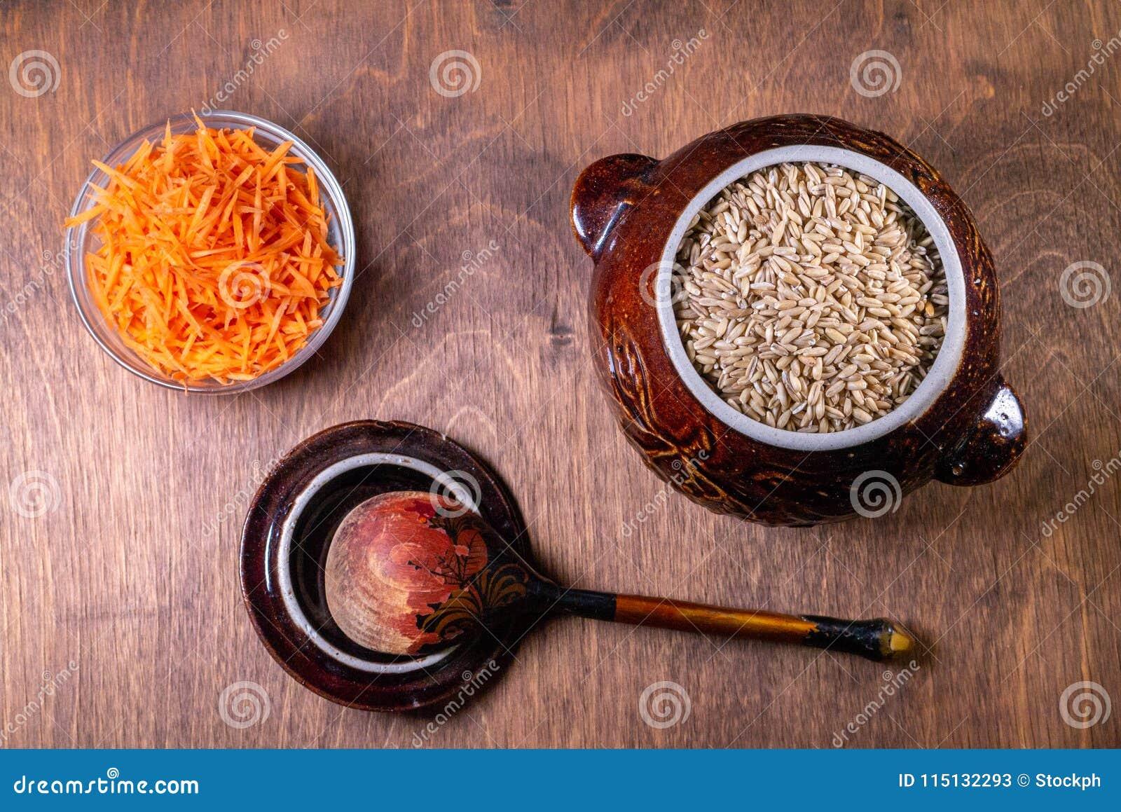 在一碗燕麦粥,有一把木匙子在它旁边,在碗的一棵切的红萝卜