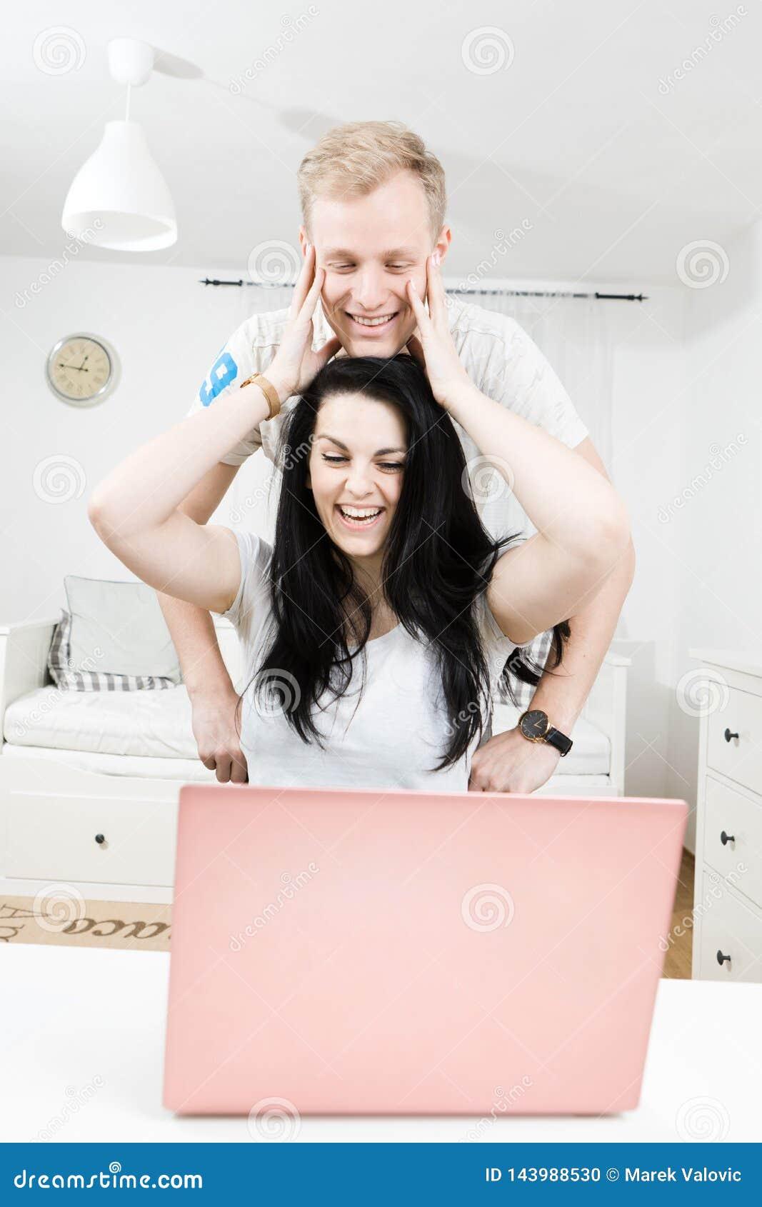 在一起在网上购物的爱的年轻有吸引力的夫妇
